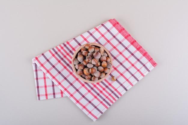 Miska łuskanych orzechów laskowych organicznych umieszczonych na białym tle. zdjęcie wysokiej jakości