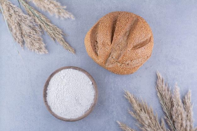 Miska mąki bochenek chleba i łodygi suszonej trawy z piór na powierzchni marmuru