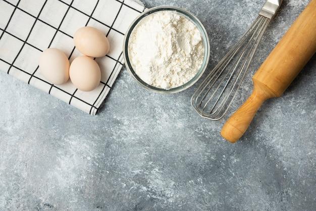 Miska mąki, jajek i narzędzi kuchennych na powierzchni marmuru.