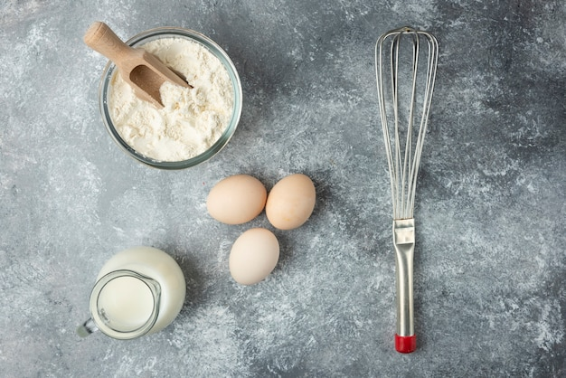 Miska mąki, jajek i wąsów na marmurowej powierzchni.