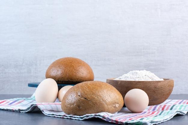 Miska mąki, jajka i bułeczki na ręczniku na marmurze.