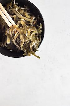 Miska marynowanej laminarii lub sałatki z jarmużu morskiego. owoce morza, wegetariańskie odżywianie i zdrowe odżywianie.