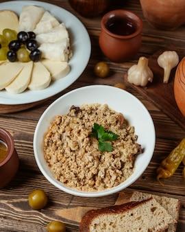 Miska mielonego mięsa z kruszonym orzechiem włoskim podana z talerzem serowym i chlebem
