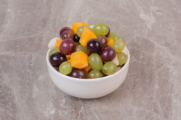 Miska mieszanych owoców na powierzchni marmuru.