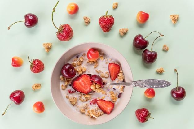 Miska musli i jogurtu ze świeżymi wiśniami, truskawkami. miseczki płatków owsianych, jagód i świeżego mleka