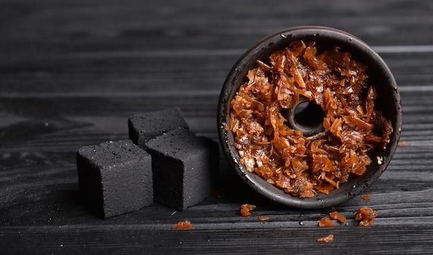 Miska na fajkę wodną z tytoniem i węglem drzewnym do palenia na ciemnym tle miejsce na tekst