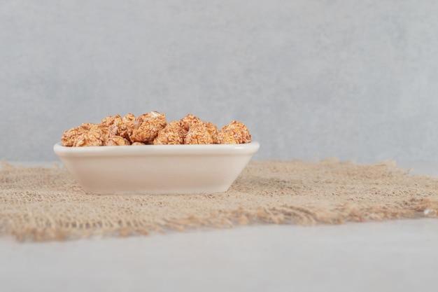 Miska na kawałku tkaniny nadziewanej brązowym kandyzowanym popcornem na marmurowym stole.