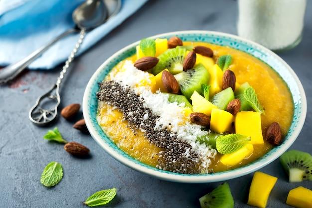 Miska na smoothie mango z kawałkami kiwi, mango, wiórkami kokosowymi i nasionami chia na kamieniu