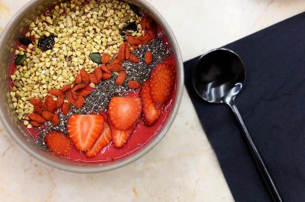 Miska na smoothie z mieszankami owoców, truskawki, goji, nasion chia i zielonej muesli gryczanej oraz metalową czarną łyżką na stole