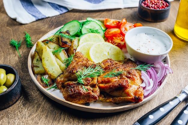 Miska obiadowa z grillowanym kurczakiem, czerwoną cebulą, pomidorem, ogórkiem, cytryną, oliwką i sause