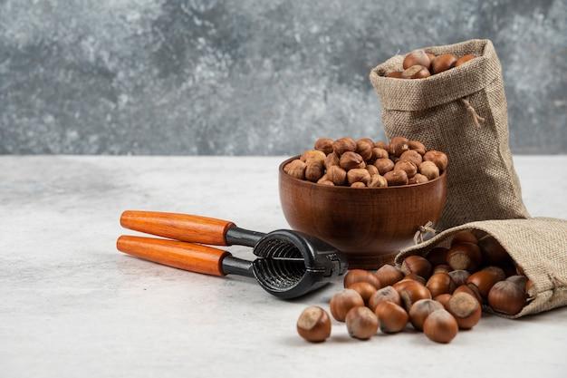 Miska organicznych jąder orzechów laskowych i łuskanych orzechów laskowych na marmurowym stole.