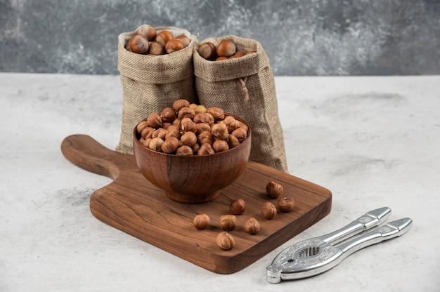 Miska organicznych jąder orzechów laskowych na desce do krojenia z łuskanymi orzechami laskowymi.