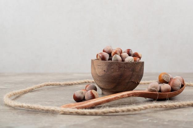 Miska orzechów laskowych, łyżka i liny na marmurowym stole.