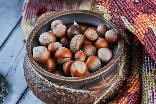 Miska orzechów laskowych na niebieskim drewnianym stole z rzeźbionym dywanikiem