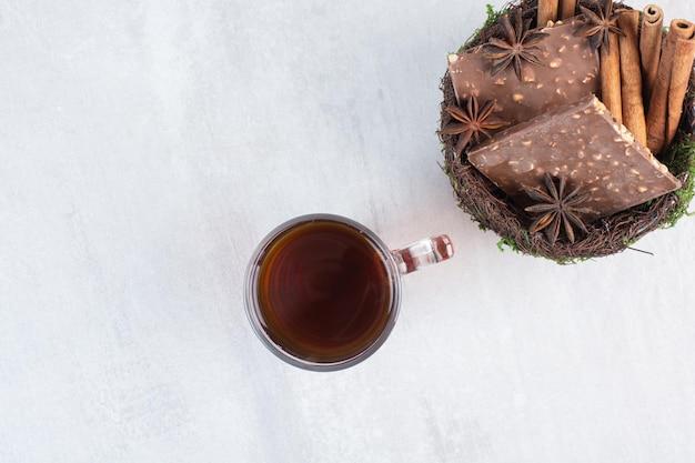 Miska orzechowej czekolady i cynamonów ze szklanką herbaty. zdjęcie wysokiej jakości