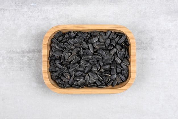 Miska pełna czarnych nasion słonecznika umieszczonych na kamieniu.