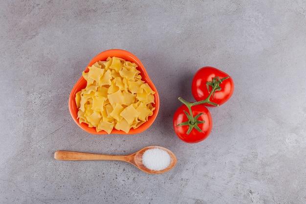 Miska pełna niegotowanego makaronu ravioli z czerwonymi świeżymi pomidorami i solą.