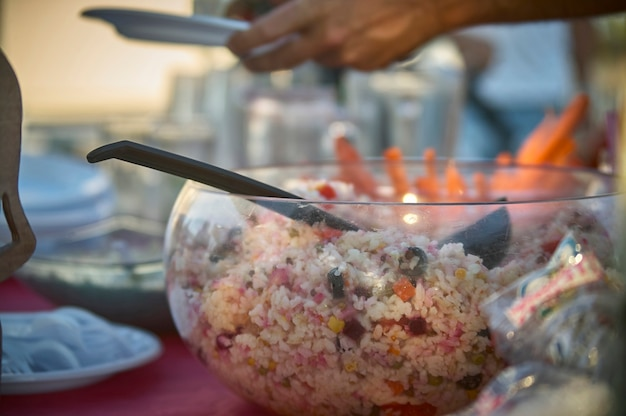 Miska pełna sałatki ryżowej odpoczywająca na stole podczas aperitif, aby zaspokoić głód bankietu. typowe danie kuchni włoskiej.