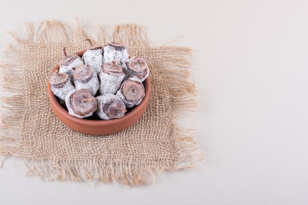 Miska pełna suszonych persimmons i konopie na białym tle. zdjęcie wysokiej jakości