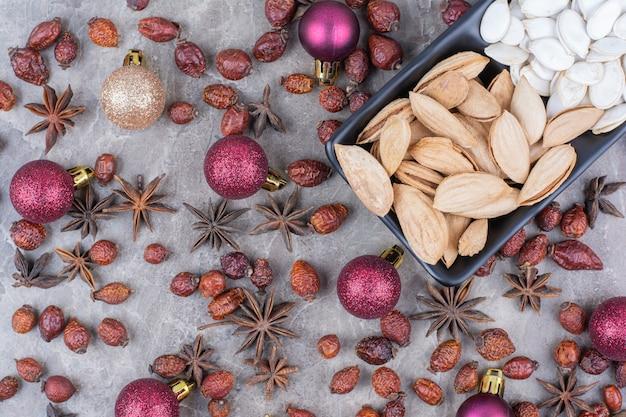 Miska pistacji i pestek dyni z owocami dzikiej róży i bombkami.