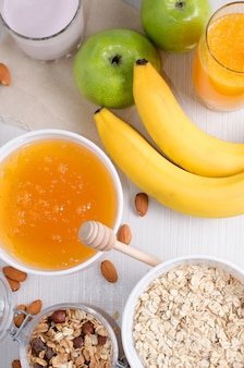 Miska płatków owsianych i rodzynek. miód, banany, zielone jabłka, orzechy