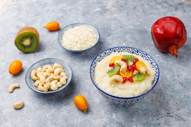Miska płatków ryżowych owsianka z plasterkami kiwi, pestkami granatu, cumquats i orzechami nerkowca, widok z góry
