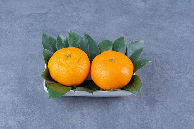 Miska pomarańczy i liści na marmurowym stole.
