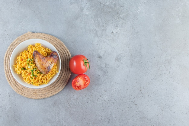 Miska pomidorów i makaronu na trójnogu, na marmurowym tle.