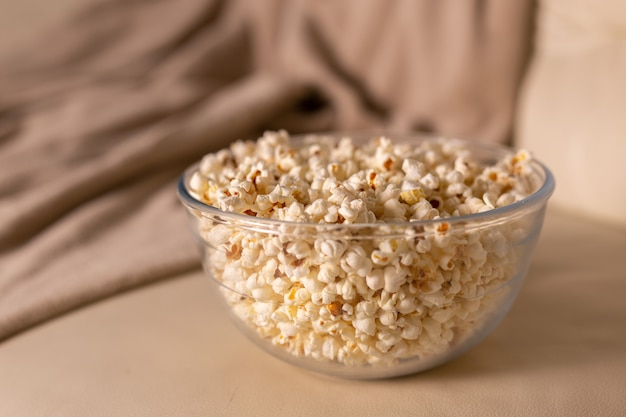 Miska popcornu do oglądania filmu na beżowej kanapie, przekąski i niezdrowa koncepcja fast foodów