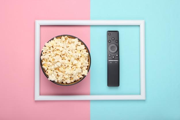 Miska popcornu i pilot do telewizora na różowo-niebieskiej pastelowej powierzchni z białą ramką