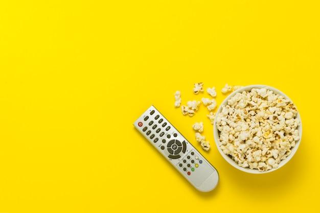 Miska popcornu i pilota do telewizora na żółtym tle. koncepcja oglądania telewizji, filmu, seriali, sportu, programów. leżał płasko, widok z góry.