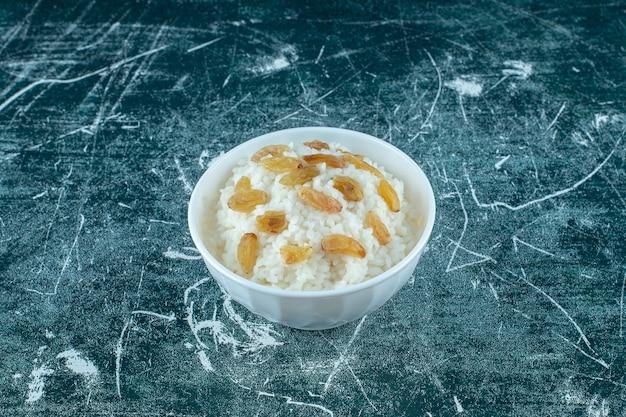 Miska puddingu ryżowego z rodzynkami, na niebieskim tle. zdjęcie wysokiej jakości
