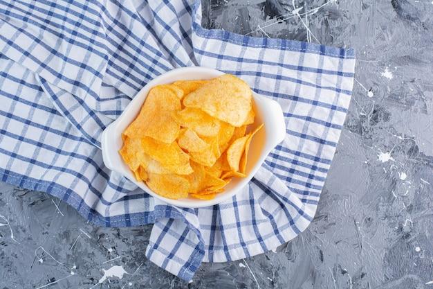 Miska pysznych chipsów ziemniaczanych na ściereczce, na marmurowej powierzchni