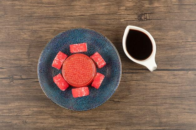 Miska rolek sushi i czerwonego kawioru na drewnianym stole z soją