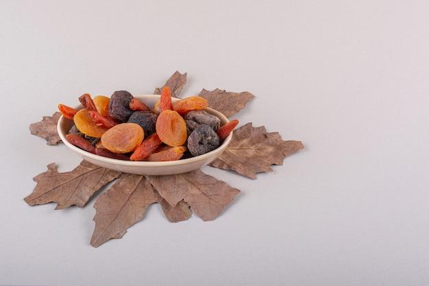 Miska różnych organicznych owoców z suchym liściem na białym tle. zdjęcie wysokiej jakości