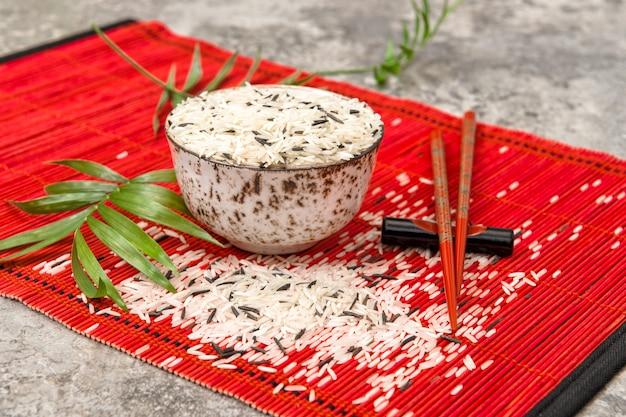 Miska ryżu pałeczki czerwona mata bambusowa. kuchnia azjatycka