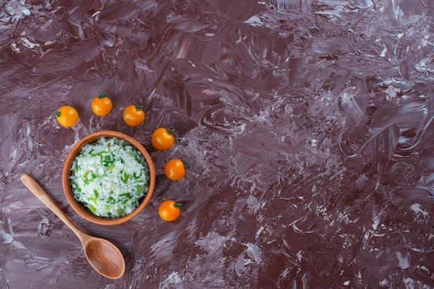 Miska ryżu, pomarańczowe pomidory i łyżka na marmurowej powierzchni