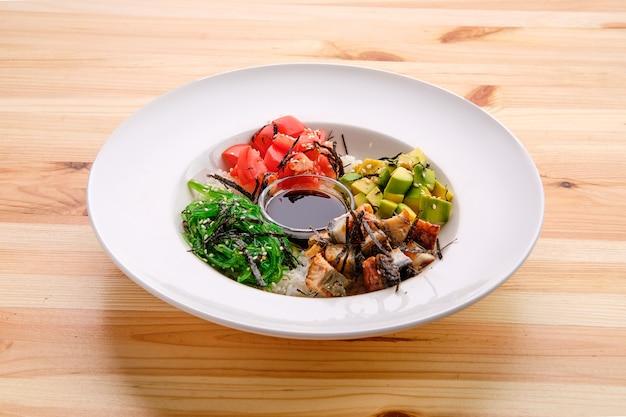 Miska ryżu sashimi unagi z awokado, wodorostami, sosem pomidorowym i sojowym