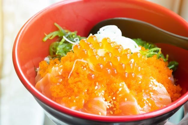 Miska ryżu zwieńczona łososiem i ikrą łososia w japońskiej restauracji