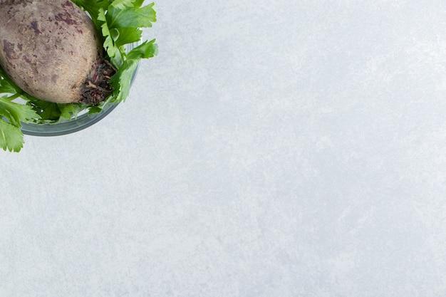 Miska rzodkiewki z natką pietruszki, na marmurowym tle.