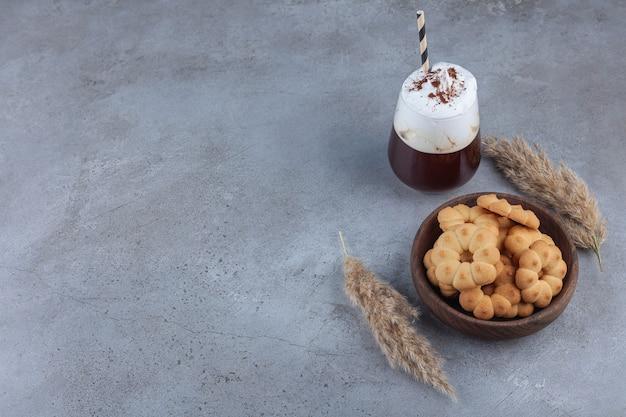 Miska słodkich ciastek ze szklanką kawy na marmurze.
