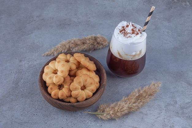 Miska słodkich ciastek ze szklanką kawy na powierzchni marmuru.