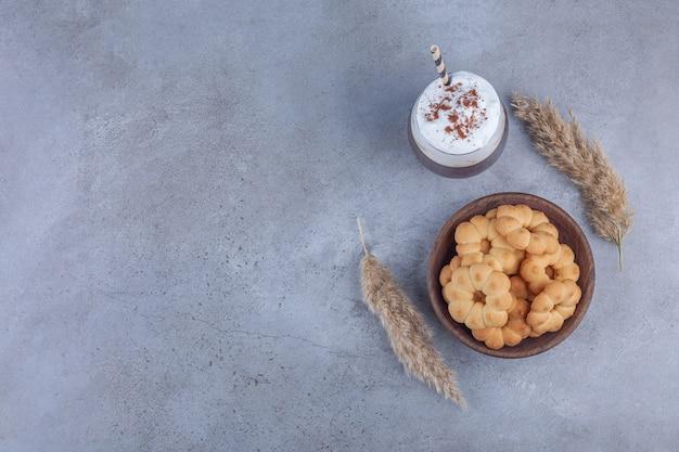 Miska słodkich ciastek ze szklanką kawy na tle marmuru.