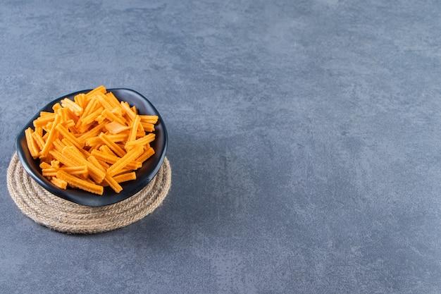 Miska słodkich frytek ziemniaczanych na trójkącie, na marmurowym tle.