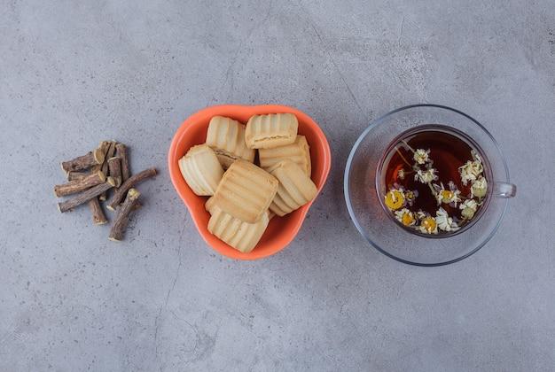 Miska słodkich herbatników i szklana filiżanka gorącej herbaty na powierzchni kamienia.