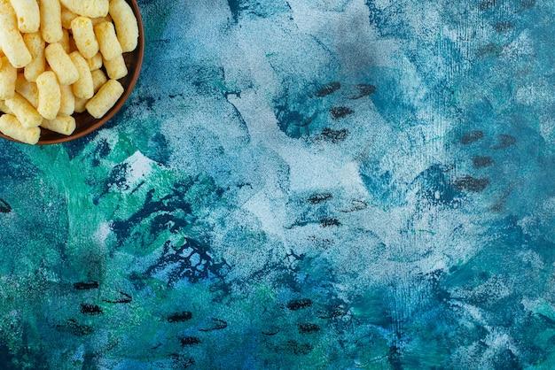 Miska słodkich paluszków kukurydzianych na niebieskim stole.
