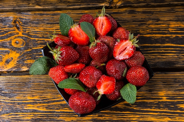 Miska smacznych dojrzałych czerwonych soczystych truskawek przyozdobionych miętą podana na rustykalnym drewnianym stole na zdrowy deser
