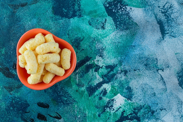 Miska smacznych paluszków kukurydzianych na niebieskim stole.