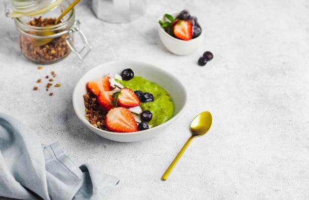 Miska smothie z awokado, bananem, szpinakiem, mlekiem kokosowym z muesli, jagodami, truskawkami i wiórkami kokosowymi. koncepcja zdrowego śniadania. żywność dla wzmocnienia odporności. widok z góry z lato