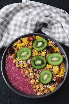 Miska śniadaniowa z koktajlem acai, płatkami owsianymi, muesli i owocami.